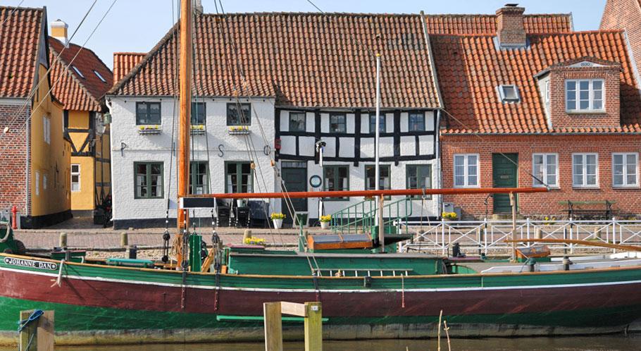 Gepflegte Bürgerhäuser am Rande der Altstadt. Ein Lastensegler im alten Hafen